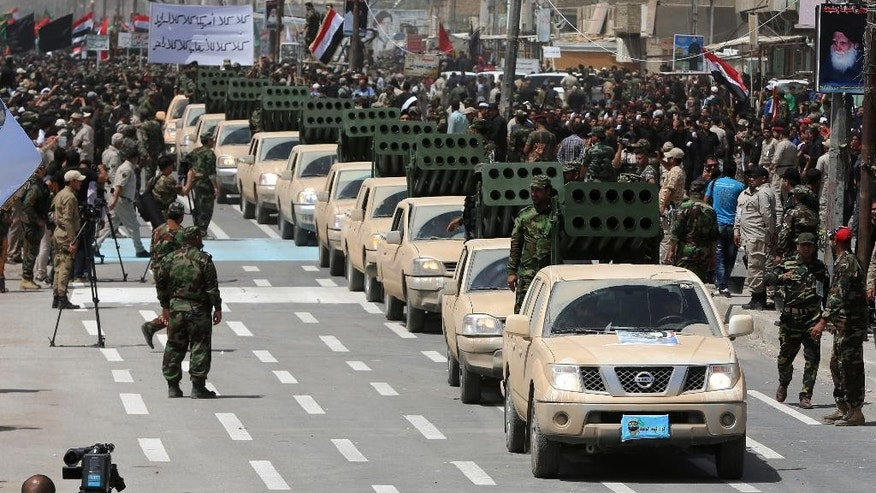 "Volunteers of the newly formed ""Peace Brigades"" participate in a parade in the Shiite stronghold of Sadr City, Baghdad, Iraq, Saturday, June 21, 2014. Thousands of Shiite militiamen have paraded in Baghdad and several other cities in southern Iraq with heavy weaponry, signaling their readiness to take on Sunni militants who control a large chunk of the country's north. (AP Photo/Karim Kadim)"