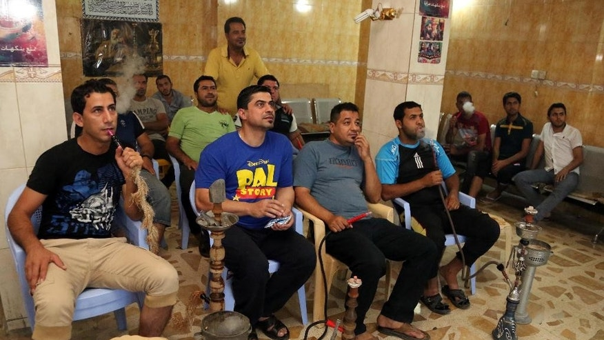 In this photo taken on June 19, 2014 Iraqi youths watch a soccer game in the World Cup at a cafe in the Shiite stronghold of Sadr City, Baghdad, Iraq. While the Iraqi capital is not under any immediate threat of falling to the Sunni militants who have captured a wide swath of the country's north and west, battlefield setbacks and the conflict's growing sectarian slant is turning this city of 7 million into an anxiety-filled place waiting for disaster to happen. (AP Photo/Karim Kadim)