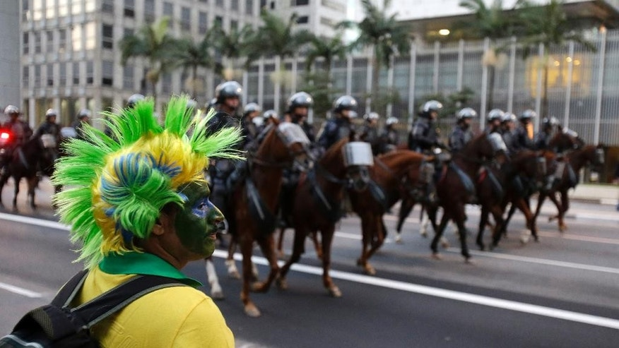 A Brazilian fan watches mounted police as they follow about 300 protesters during a rally against the soccer World Cup in Sao Paulo, Brazil, Monday, June 23, 2014. (AP Photo/Thanassis Stavrakis)