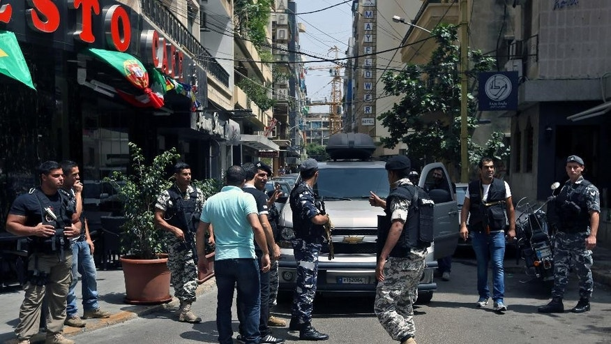 FILE - In this file photo taken Friday, June 20, 2014, Lebanese police intelligence gather outside a hotel in Hamra street in Beirut, Lebanon. An al-Qaida breakaway group's seizure of territory in Iraq and Syria has sent tremors across the Middle East, jolting neighboring countries into action over fears that the Islamic militants may set their sights on them next. In Lebanon heavily armed police busted a suspected sleeper cell allegedly linked to the group, known as the Islamic State of Iraq and the Levant, in raids on two hotels in central Beirut. (AP Photo/Bilal Hussein, File)