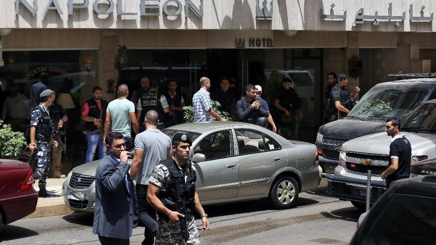 FILE - In this file photo taken Friday, June 20, 2014, Lebanese police intelligence gather outside a hotel after security forces raided it in Beirut's Hamra district, Lebanon. An al-Qaida breakaway group's seizure of territory in Iraq and Syria has sent tremors across the Middle East, jolting neighboring countries into action over fears that the Islamic militants may set their sights on them next. In Lebanon heavily armed police busted a suspected sleeper cell allegedly linked to the group, known as the Islamic State of Iraq and the Levant, in raids on two hotels in central Beirut. (AP Photo/Bilal Hussein, File)