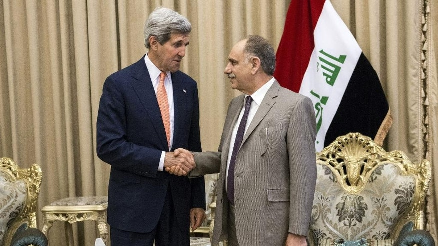 Iraqi Deputy Prime Minister Saleh al-Mutlaq, right, greets U.S. Secretary of State John Kerry before a meeting in the capital Baghdad, Iraq, Monday, June 23, 2014. Kerry said the fate of Iraq may be decided over the next week and is largely dependent on whether its leaders meet a deadline for starting to build a new government. (AP Photo/Brendan Smialowski, Pool)