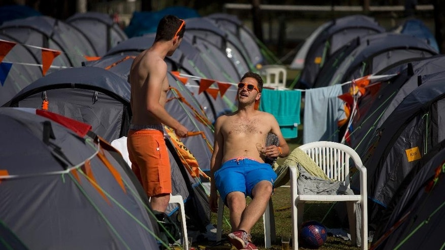 Dutch fans relax at the Oranjecamping site during the 2014 soccer World Cup in Sao Paulo, Brazil, Sunday, June 22, 2014. It's not simple to stand out during the World Cup in Brazilian stadiums carpeted by yellow and green. But along the edges of a dam in the southern part of Sao Paulo, Dutch soccer fans have built a camp for 500 people, creating a spot where orange is the new yellow. (AP Photo/Dario Lopez-Mills)