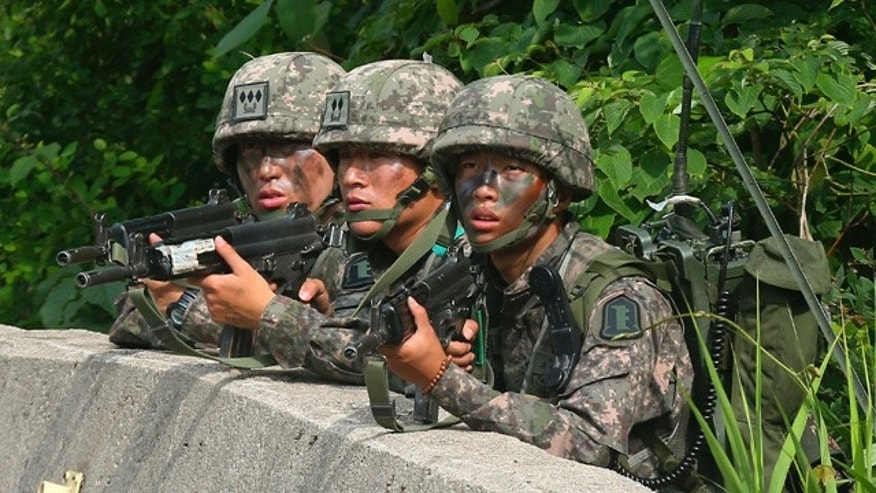 June 23, 2014: South Korean army soldiers aim their machine guns during an arrest operation in Goseong. The parents of a runaway South Korean soldier suspected of killing five comrades at an outpost near the tense border with North Korea pleaded with him to surrender Monday as the military were besieging him and trying to capture him alive, officials said. (AP Photo/Yonhap, Hwang Kwang-mo)