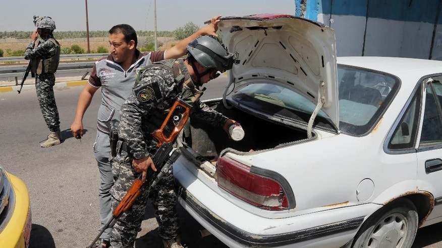 An Iraqi federal policeman stands guard as his colleague searches a car at a checkpoint in Baghdad, Iraq, Sunday, June 22, 2014. Sunni militants have seized another town in Iraq's western Anbar province, the fourth to fall in two days, officials said Sunday, in what is shaping up to be a major offensive in one of Iraq's most restive regions. (AP Photo/Karim Kadim)
