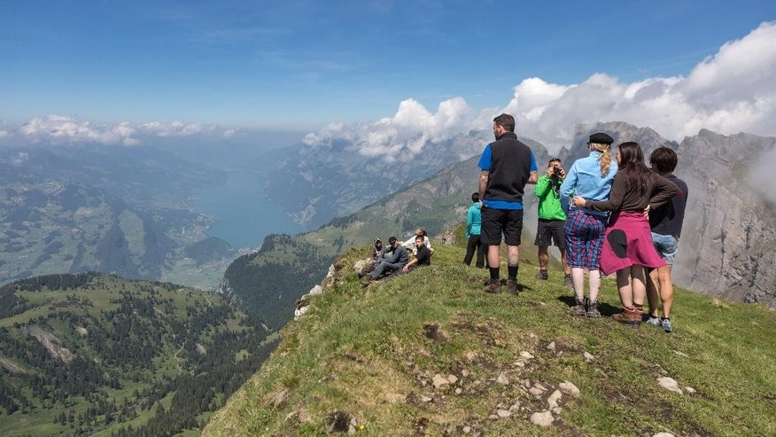 In this picture taken Saturday June 21, 2104, hikers enjoy the view from the Alvier mountain  in the Swiss Alps near Truebbach , Switzerland. (AP Photo/Keystone,Arno Balzarini)