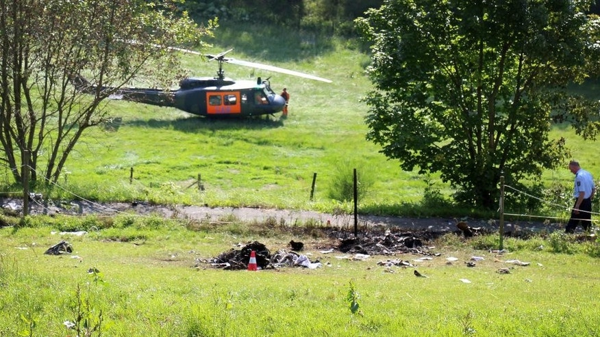 A helicopter has landed near debris of a crashed Learjet near Elpe, Germany, Monday, June 23, 2014. The Learjet with two persons on board collided with a Eurofigher of German airforce which landed safely at its base in Noervenich. (AP Photo/dpa, Joerg Taron)