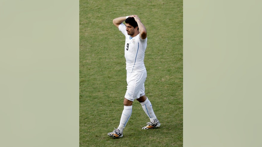 Uruguay's Luis Suarez walks with his hands on his head during the group D World Cup soccer match between Italy and Uruguay at the Arena das Dunas in Natal, Brazil, Tuesday, June 24, 2014. (AP Photo/Hassan Ammar)