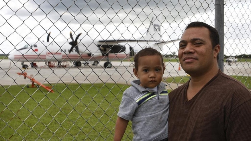 In this Wednesday, June 4, 2014 photo, Sau Tongi, holding his son, stands in front of a China-made MA-60 plane on the tarmac at Fua'amotu Domestic Airport in Nuku'alofa, Tonga. New Zealand tourists attracted by the country's beauty have been staying away due to a dispute over the safety of the plane. The dispute represents a small skirmish in a broader battle for global influence. (AP Photo/Nick Perry)