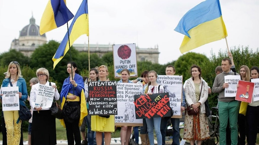 Demonstrators  with Ukrainian flags protest against Russian President Vladimir Putin on occasion of his visit to Austrian President Heinz Fischer in front of Vienna's historic Hofburg palace  Tuesday June 24, 2014. Putin is on a one-day visit to Austria. (AP Photo/Herwig Prammer)