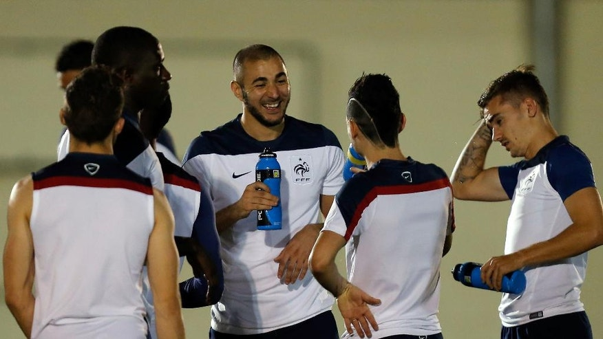 France's Karim Benzema, center, jokes with teammates during an official training session at the Joao Havelange Olympic stadium, in Rio de Janeiro, Brazil, Tuesday, June 24, 2014. France will play its next game against Ecuador in group E of the 2014 soccer World Cup. A draw is enough to guarantee top spot for France, and would also send Ecuador through to the next round if Switzerland fails to beat Honduras in the other match. (AP Photo/David Vincent)