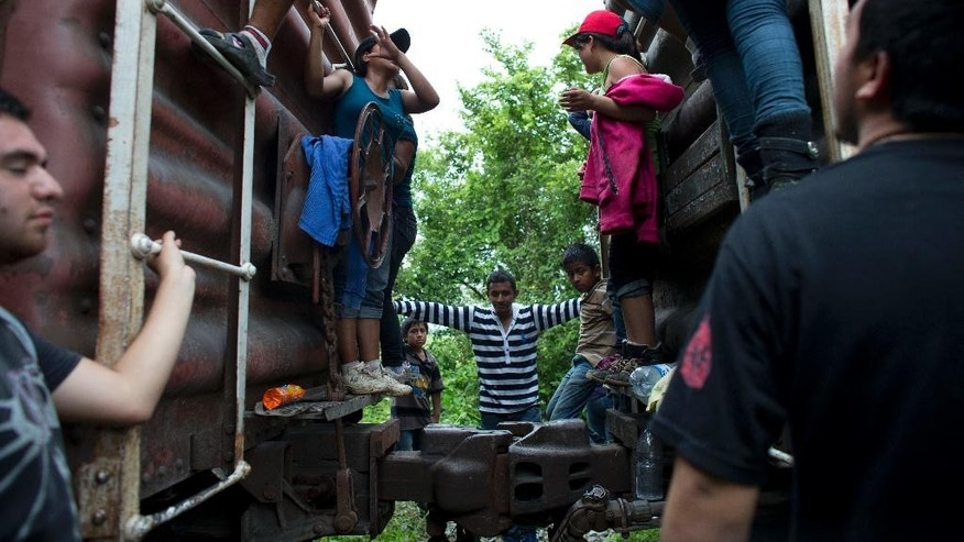 In this Friday, June 20, 2014 photo, Central American migrants hang out around the northbound freight train they had been traveling on, after it suffered a minor derailment in a remote wooded area outside Reforma de Pineda, Chiapas state, Mexico. The train remained stuck for a day and a half, exposing the migrants to the possibility of attacks by criminal gangs. The Beta squad, a governmental group dedicated to the protection of migrants, brought water to the stranded travelers and offered medical care. (AP Photo/Rebecca Blackwell)