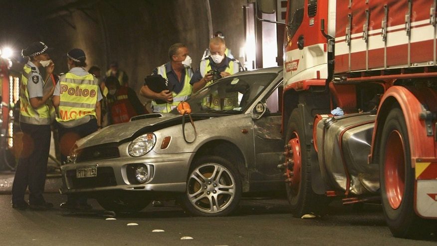 MELBOURNE, AUSTRALIA - MARCH 23:  Police officers and investigators inspect a vehicle involved at the crash site inside Melbourne's Burnley Tunnel are seen after a fatal collision on March 23, 2007 in Melbourne, Australia. Hundreds of motorists were ordered to abandon their cars and flee the tunnel after up to three trucks and four cars were involved in a pile-up that caused an explosion.  (Photo by David Caird-Pool/Getty Images)