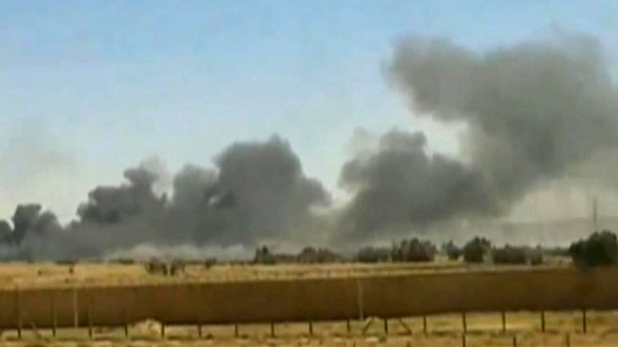 June 25, 2014: This image made from video posted on a pro-militant social media account, which has been verified and is consistent with other AP reporting, shows smoke rising in the skyline during fighting between Al Qaeda inspired militants and Iraqi security forces at the Beiji oli refinery in northern Iraq.