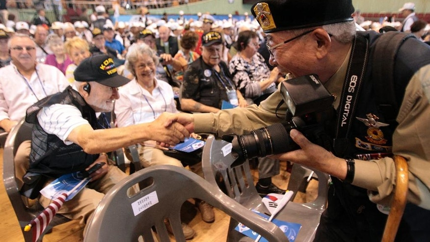 U.S. veteran  Fred R. Liberhan from Brooklyn, N.Y., left, shakes hands with South Korean war veteran Lee Gang-sung during a ceremony to mark the 64th anniversary of the outbreak of the Korean War in Seoul, South Korea, Wednesday, June 25, 2014. The three year Korean War broke out on June 25, 1950, when Soviet tank-led North Koreans invaded South Korea. (AP Photo/Ahn Young-joon)