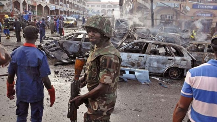 June 25, 2014: A Nigerian soldier,  center, walks, at the scene of an  explosion in Abuja, Nigeria. (AP)