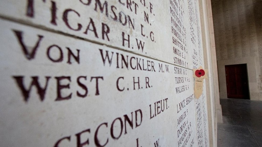 A wooden remembrance with a poppy is placed near names of the missing on the Menin Gate in Ypres, Belgium on Thursday, June 26, 2014. European Union heads of state will gather on Thursday for the first day of an EU summit in the city Ypres and will participate in a ceremony to commemorate the outbreak of World War I under the Menin Gate.  (AP Photo/Virginia Mayo)