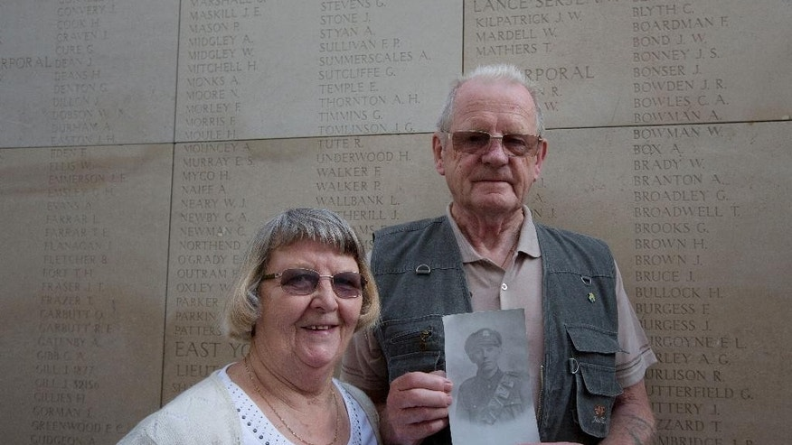 Alan Siggee, from Swineshead, Linconshire, England, right, stands with his wife Audrey as he holds a photo of his father, World War I soldier Arthur Siggee, during a visit to the Menin Gate in Ypres, Belgium on Thursday, June 26, 2014. European Union heads of state will gather on Thursday for the first day of an EU summit in the city Ypres and will participate in a ceremony to commemorate the outbreak of World War I under the Menin Gate.  (AP Photo/Virginia Mayo)