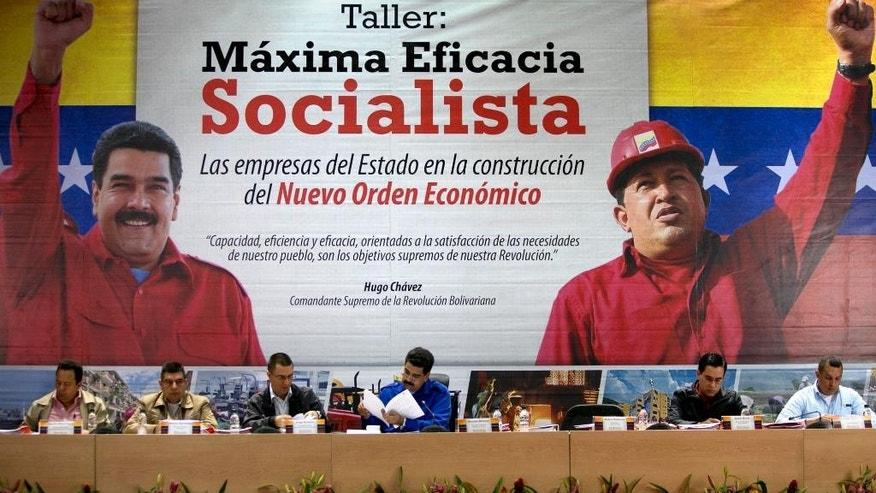"FILE - In this Feb. 8, 2014 file photo, Venezuela's President Nicolas Maduro, center, leads a workshop for state workers in front of a banner showing Maduro, left, and Venezuela's former President Hugo Chavez and reads in Spanish ""Workshop: Maximum Socialist Effectiveness. State companies in the construction of the new economic order, "" at the headquarters of Petroleos de Venezuela S.A. (PDVSA) oil compnay in Caracas, Venezuela. Maduro was tapped by Chavez as his preferred successor to the presidency, and is quick to invoke the late leader's name, but orthodox socialists are grumbling over free-market reforms they say are counter to the revolution. (AP Photo/Alejandro Cegarra, File)"