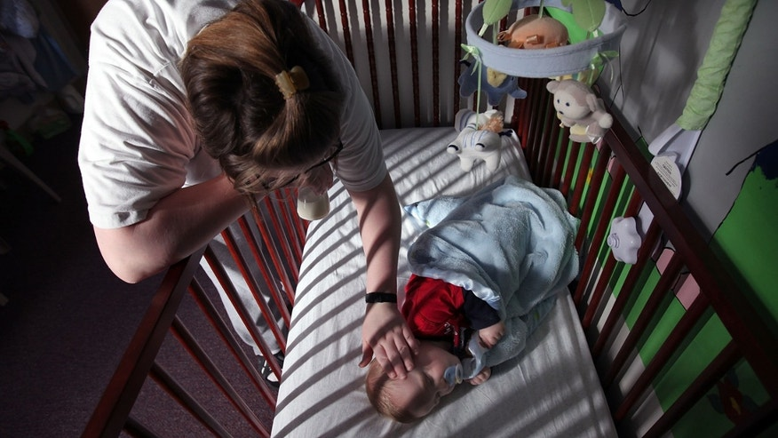 DECATUR, IL - FEBRUARY 18:  Katrisa Parks puts her eight-month-old son Skyler down for a nap in the room they share at the Decatur Correctional Center February 18, 2011 in Decatur, Illinois. Skyler, who was born while Parks was serving a ten-year sentence for burglary, lives with his mother at the prison, part of the Moms with Babies program at the minimum security facility. The program allows incarcerated women to keep their newborn babies with them for up to two years while serving their sentence. The program boasts a zero percent recidivism rate compared to the statewide rate of 51.3 percent.  (Photo by Scott Olson/Getty Images)
