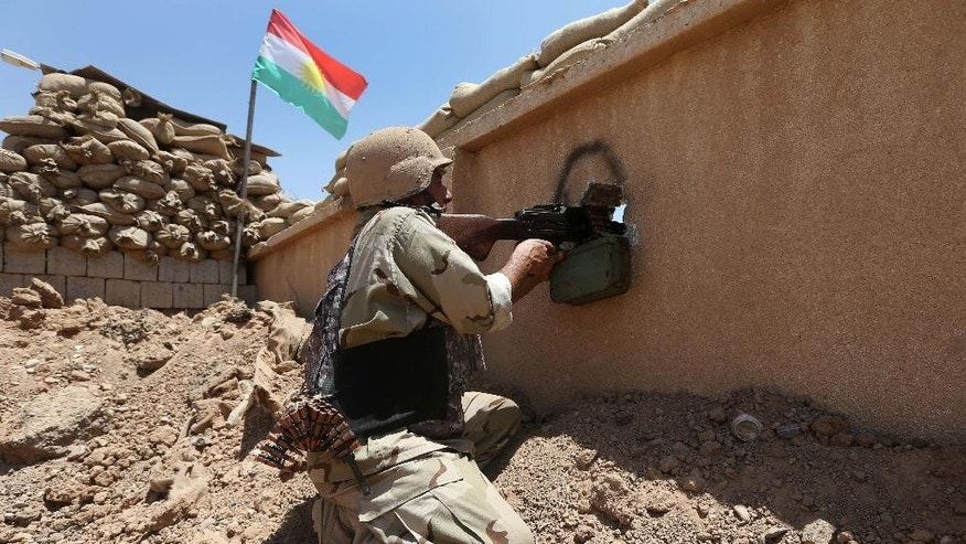 "A Kurdish peshmerga fighter takes his position behind a wall on the front line with militants from the al-Qaida-inspired Islamic State in Iraq and the Levant (ISIL), in Tuz Khormato, 100 kilometers (62 miles) south of the oil rich province of Kirkuk, northern Iraq, Wednesday, June 25, 2014. A defiant Prime Minister Nouri al-Maliki rejected calls Wednesday for an interim ""national salvation government"" intended to undermine the Sunni insurgency by presenting a unified front among Iraq's three main groups, calling it a ""coup against the constitution."" (AP Photo/Hussein Malla)"