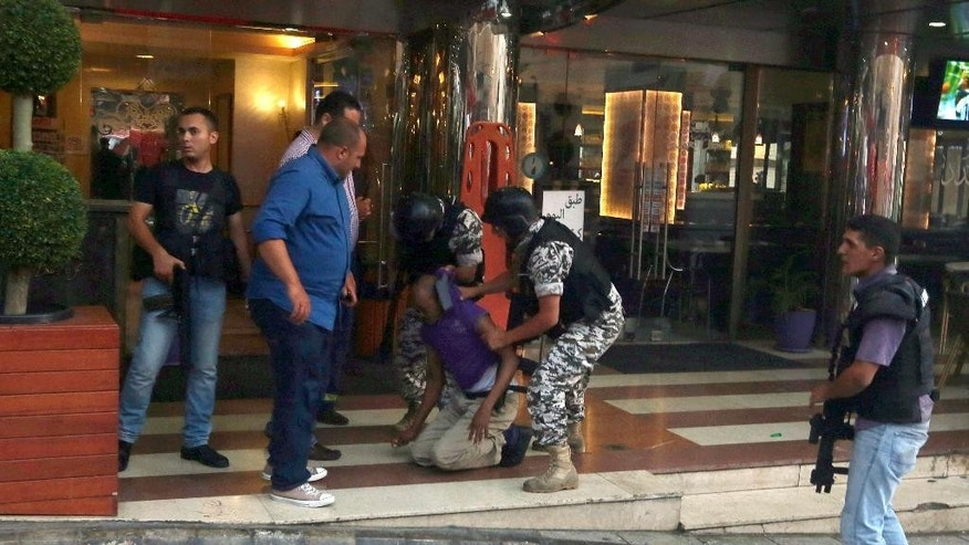 Lebanese security forces detain a man outside the Duroy hotel where a suicide bomber blew himself up in his room, in Beirut, Lebanon, Wednesday, June 25, 2014, as Lebanese security forces raided the premises. The bombing is the latest in a string of attacks and security sweeps in Lebanon over the past week that have sparked fears of renewed violence in a country that has been deeply affected by the civil war in neighboring Syria.(AP Photo/Bilal Hussein)