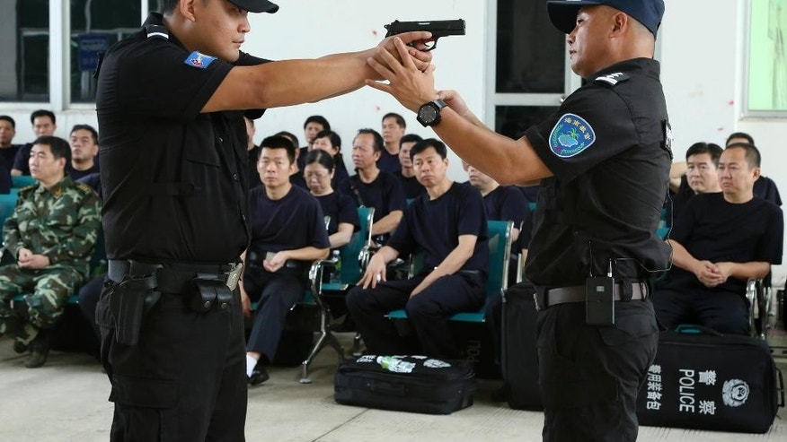 In this April 25, 2014 photo, a police training officer, right, guides a trainee during a weapons training session for police officers in Haikou, in southern China's Hainan province. By arming its patrolling officers, China has abandoned its decades-old policy of unarmed local police in response to concerns over crime and terrorism, leaving Britain, Norway and New Zealand among the major countries where regular patrolling police still generally do not carry arms. (AP Photo)  CHINA OUT