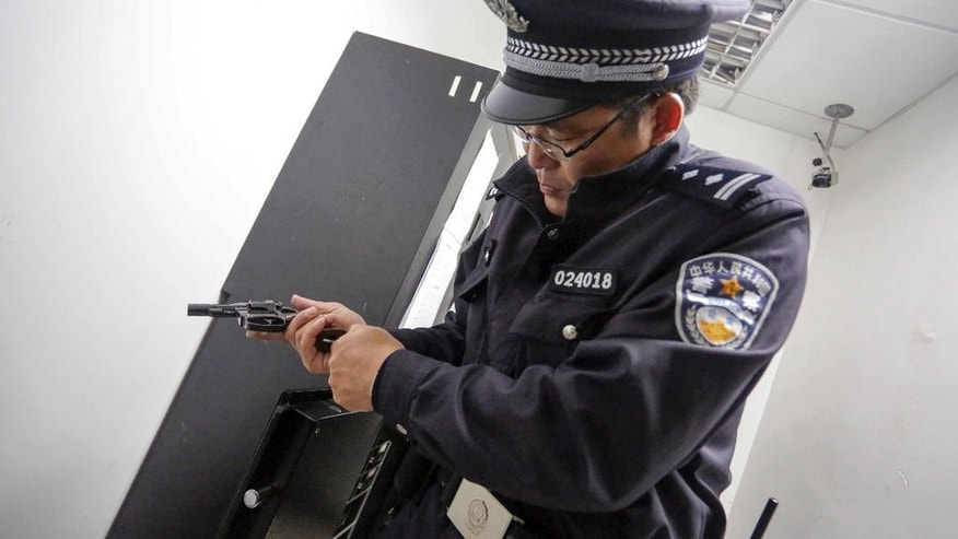 FILE - In this April 20, 2014 file photo, a Chinese policeman checks his pistol before going on patrol in Shanghai, China. By arming its patrolling officers, China has abandoned its decades-old policy of unarmed local police in response to concerns over crime and terrorism, leaving Britain, Norway and New Zealand among the major countries where regular patrolling police still generally do not carry arms. (AP Photo, File) CHINA OUT