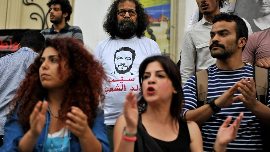 This photo dated May 22, 2014, shows Tunisian activists staging a demonstration in front of the Tunis courthouse in Tunisia in support of a jailed blogger. The arrest for drug possession of Aziz Amami, a prominent blogger from the 2011 revolution that overthrew Tunisia's police state, prompted protests and a renewed effort to amend draconian drug laws that many say are used by police to abuse their enemies. (AP Photo/Ilyess Osmane)