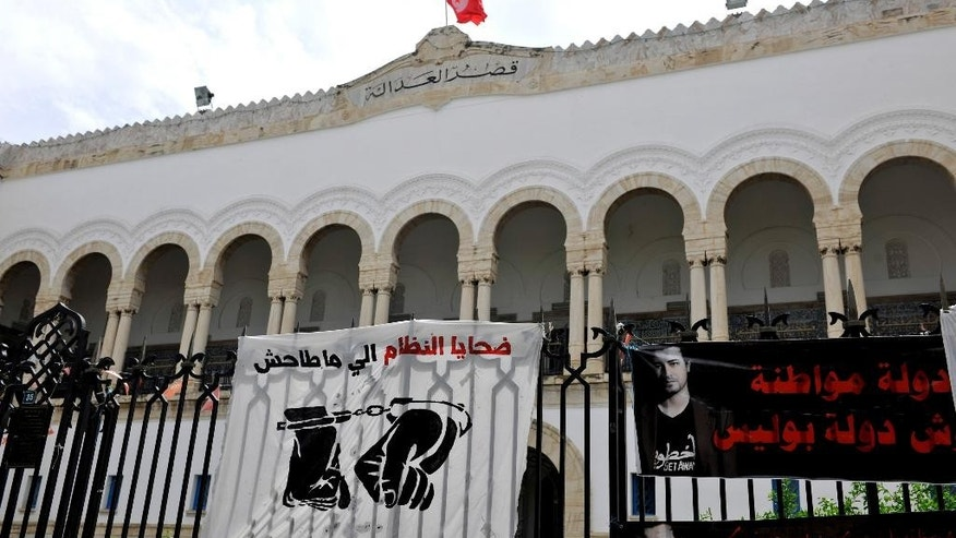 This photo dated May 23, 2014, shows banners hanging on the fence of the Tunis courthouse in Tunisia in support of a blogger. The arrest for drug possession of Aziz Amami, a prominent blogger from the 2011 revolution that overthrew Tunisia's police state, prompted protests and a renewed effort to amend draconian drug laws that many say are used by police to abuse their enemies. (AP Photo/Ilyess Osmane)