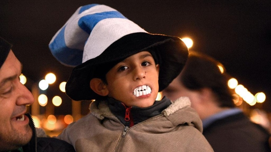 A child shows his support for Uruguay player Luis Suarez, by wearing toy plastic vampire's teeth, as he awaits the arrival of Suarez at Carrasco International Airport in the outskirts of Montevideo, Uruguay, Thursday, June 26, 2014. The Uruguay forward, widely regarded as one of the best players in the world, was banned by FIFA from all football for four months on Thursday for biting an Italian opponent in an incident that marred the team's victory and progression to the second round. (AP Photo/Matilde Campodonico)