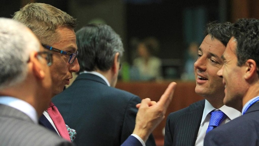 Finland's Prime Minister Alexander Stubb, left, gestures as he talks with  Italy's Prime Minister Matteo Renzi, 2nd right, during an EU Summit meeting in Brussels on Friday, June 27, 2014. European Union leaders are set to nominate former Luxembourg Prime Minister Jean-Claude Juncker to become the 28-nation bloc's new chief executive despite strong British opposition. The leaders at their summit Friday in Brussels planned to elect Juncker with overwhelming majority as the candidate they will propose to the European Parliament.  (AP Photo/Yves Logghe)