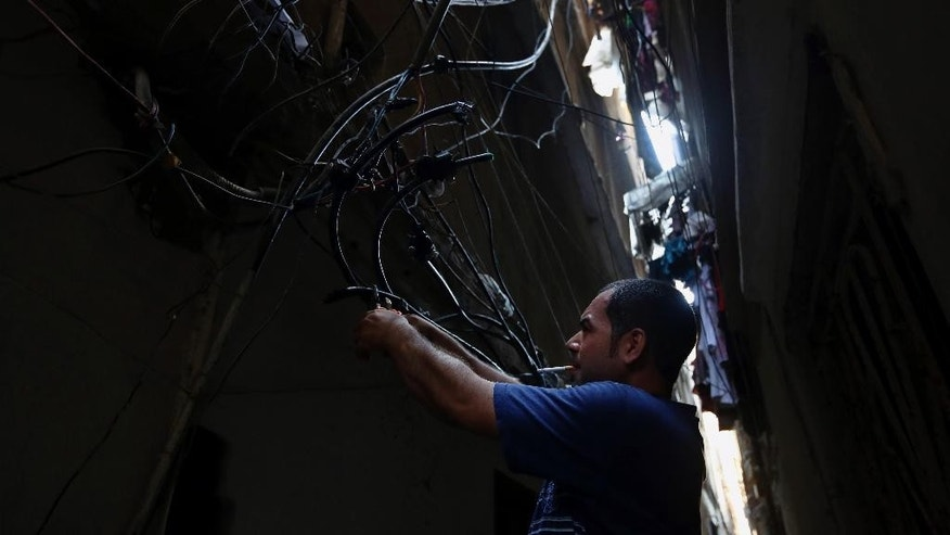 In this May 24, 2014 photo, Abu Wadiyeh, a 34-year-old Palestinian who was born in Syria, fixes power cables at the Palestinian refugee camp of Shatila in Beirut, Lebanon. One look at the jumbled mass of sinewy electricity cables, TV and Internet lines that droop over the damp, narrow alleyways of the Palestinian refugee camp of Shatila, and it's easy to see why. Wadiyeh, chief electrician in Shatila, is responsible for making order out of that chaos to ensure that the camp's more than 20,000 residents can turn on their lights and televisions. (AP Photo/Bilal Hussein)