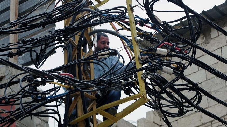 In this May 21, 2014 photo, Abu Wadiyeh, a 34-year-old Palestinian who was born in Syria, fixes power cables at the Palestinian refugee camp of Shatila in Beirut, Lebanon. One look at the jumbled mass of sinewy electricity cables, TV and Internet lines that droop over the damp, narrow alleyways of the Palestinian refugee camp of Shatila, and it's easy to see why. Wadiyeh, chief electrician in Shatila, is responsible for making order out of that chaos to ensure that the camp's more than 20,000 residents can turn on their lights and televisions. (AP Photo/Bilal Hussein)