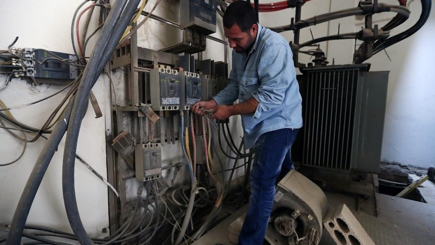 In this May 21, 2014 photo, Abu Wadiyeh, a 34-year-old Palestinian who was born in Syria, works a power station at the Palestinian refugee camp of Shatila in Beirut, Lebanon. One look at the jumbled mass of sinewy electricity cables, TV and Internet lines that droop over the damp, narrow alleyways of the Palestinian refugee camp of Shatila, and it's easy to see why. Wadiyeh, chief electrician in Shatila, is responsible for making order out of that chaos to ensure that the camp's more than 20,000 residents can turn on their lights and televisions. (AP Photo/Bilal Hussein)