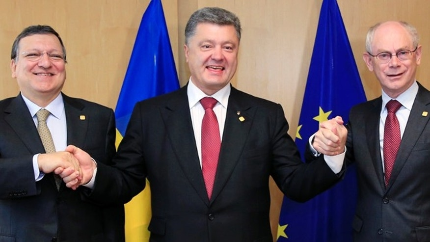 June 27, 2014: Ukraine's President Petro Poroshenko poses with European Commission President Jose Manuel Barroso (L) and European Council President Herman Van Rompuy (R) at the EU Council in Brussels.