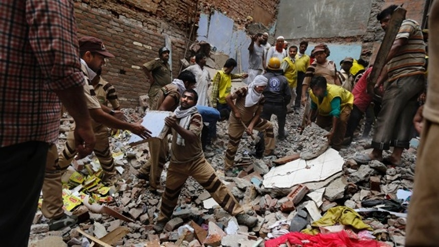 June 28, 2014: Rescue workers clear debris at the site of a building collapse in New Delhi, India. (AP Photo/Altaf Qadri)