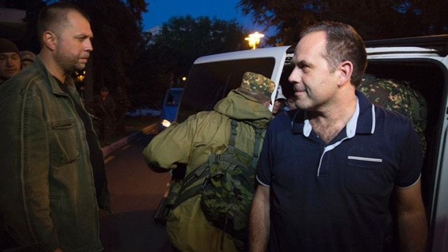 June 28, 2014: An unidentified member of the OSCE Special Monitoring Mission in Ukraine gets out of a vehicle next to Alexander Borodai, Prime Minister of the self proclaimed 'Donetsk People's Republic', left, on arrival in the city of Donetsk, eastern Ukraine. (AP Photo/Dmitry Lovetsky)