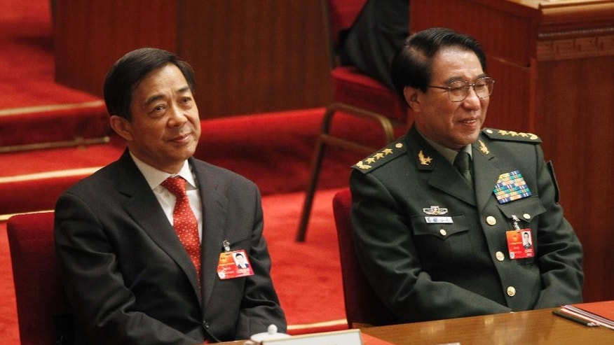 FIEL - In this March 14, 2012 file photo, Xu Caihou, right, deputy chairman of the CPC Central Military Commission, which controls China's military, and Chongqing party secretary Bo Xilai attend the closing session of the National People's Congress at the Great Hall of the People in Beijing, China. A spreading anti-corruption crackdown launched by President Xi Jinping snared its most senior figure to date on Monday, June 30, 2014 when the former top Chinese general was expelled from the ruling Communist Party to face bribery charges. Gen. Xu, is accused of taking money and property in exchange for promotions and other favors, said a party statement reported by the official Xinhua News Agency. It said his case had been handed over to military prosecutors. (AP Photo/Vincent Thian, File)
