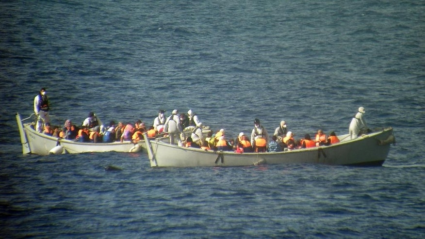 In this photo released by the Italian Navy on Monday, June 30, 2014, and taken on Sunday, June 29, 2014, two lifeboats from the Italian frigate Grecale carries a group of migrants rescued in the Mediterranean Sea. The bodies of some 30 would-be migrants were found in in the hold of a packed smugglers' boat making its way to Italy, the Italian navy said Monday. The boat was carrying nearly 600 people, and the remaining 566 survivors were rescued by the navy frigate Grecale and were headed to the port at Pozzallo, on the southern tip of Sicily. (AP Photo/Italian Navy, ho)