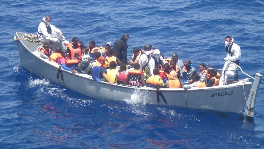 In this photo released by the Italian Navy on Monday, June 30, 2014, and taken on Sunday, June 29, 2014, a lifeboat from the Italian frigate Grecale carries a group of migrants rescued in the Mediterranean Sea. The bodies of some 30 would-be migrants were found in in the hold of a packed smugglers' boat making its way to Italy, the Italian navy said Monday. The boat was carrying nearly 600 people, and the remaining 566 survivors were rescued by the navy frigate Grecale and were headed to the port at Pozzallo, on the southern tip of Sicily. (AP Photo/Italian Navy, ho)