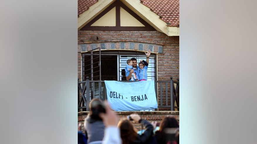 Uruguay's soccer player Luis Suarez, with his children Benjamin, left, and Delfina, waves to fans from his home, before the start of his team's World Cup round 16 match with Colombia, on the outskirts of Montevideo, Uruguay, Saturday, June 28, 2014. FIFA banned Suarez from all football activities for four months for biting an opponent at the World Cup, a punishment that rules him out of the rest of the tournament. (AP Photo/Matilde Campodonico)