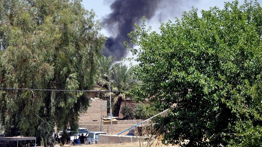 In this photo taken on Saturday, June 28, 2014, smoke rises during a military operation to regain control of Dallah Abbas north of Baqouba, the capital of Iraq's Diyala province, 35 miles (60 kilometers) northeast of Baghdad, Iraq. The Islamic State in Iraq and the Levant which already controls vast swaths in northern and eastern Syria amid the chaos of that nation's civil war, aims to erase the borders of the modern Middle East and impose its strict brand of Shariah law. (AP Photo)