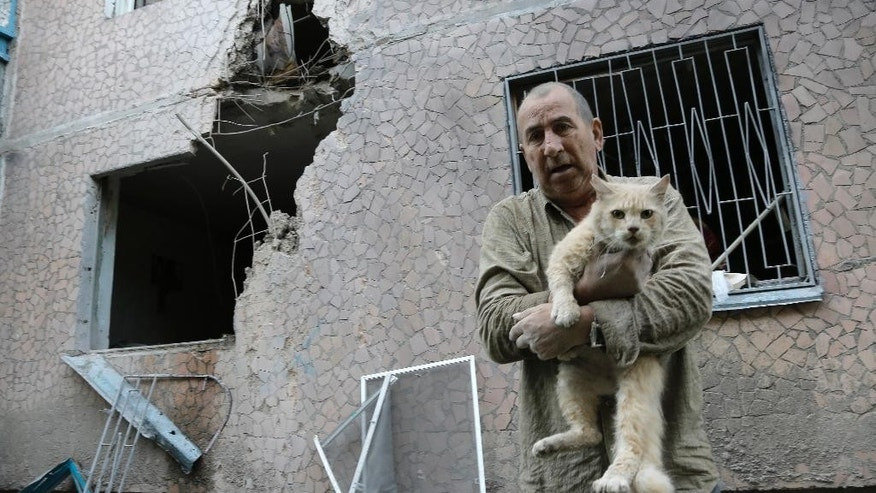 CORRECTS THE CONDITION OF THE  CAT  Valery who gave only his first name carries his injured cat in front of his damaged house after shelling in the city of Slovyansk, Donetsk Region, eastern Ukraine Monday, June 30, 2014. Residential areas came under shelling on Monday morning from government forces. (AP Photo/Dmitry Lovetsky)