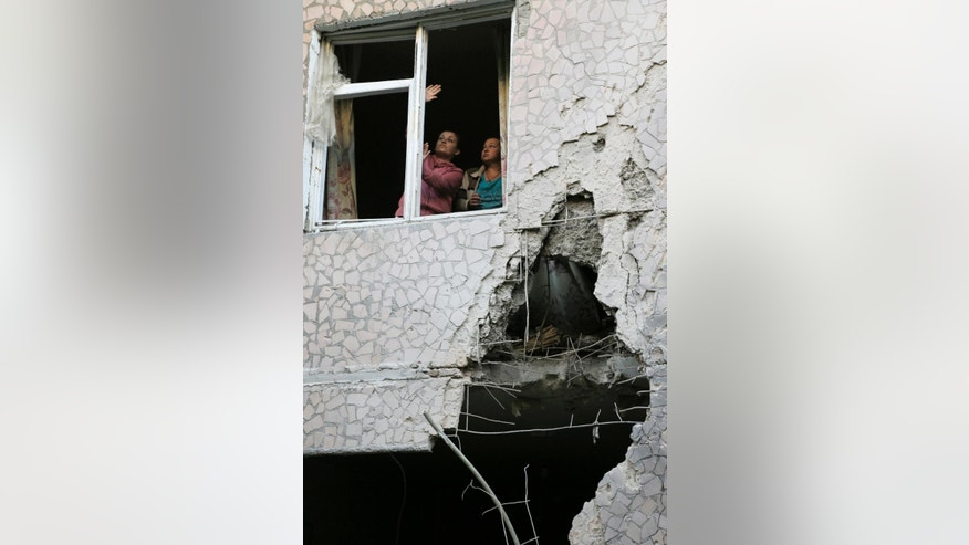Women try to open a window in their damaged house after shelling in the city of Slovyansk, Donetsk Region, eastern Ukraine Monday, June 30, 2014. Residential areas came under shelling on Monday morning from government forces. (AP Photo/Dmitry Lovetsky)
