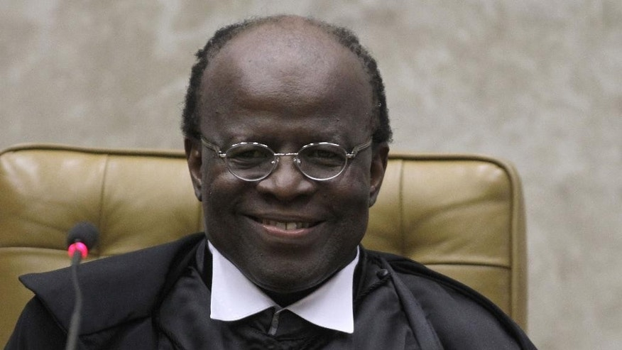 FILE - In this  Nov. 22, 2012 file photo, Brazil's Supreme Court President Joaquim Barbosa smiles during his inauguration ceremony at the Supreme Court in Brasilia, Brazil. Barbosa, Brazil's first and only black top court justice, is presiding over his last session as president of the Supreme Court on Tuesday, July 1, 2014. Barbosa announced his early retirement one month ago. (AP Photo/Eraldo Peres, File)
