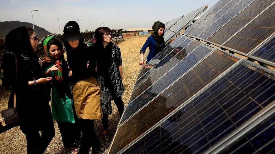 In this June, 22, 2014 photo, Iranian students tour the Taleghan Renewable Energy Site in Taleghan,160 kilometers (99 miles) northwest of capital Tehran, Iran. Solar has been a hot topic of discussion in Iran, which this year fielded a team of university students to compete in a U.S. solar car contest in July. Saman Mirhadi, a senior government official, said the government installed solar panels at some 1,000 locations across Iran, including the rooftops of mosques, schools and government buildings. (AP Photo/Ebrahim Noroozi)