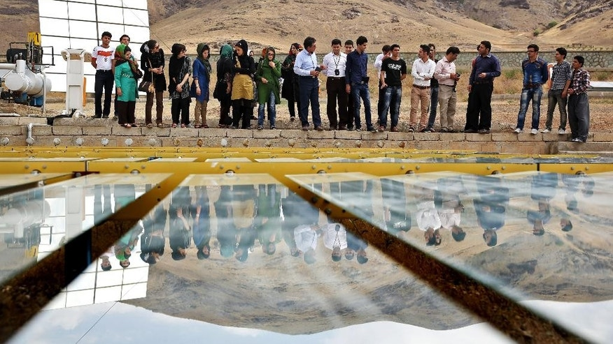 In this June, 22, 2014 photo, Iranian students tour the Taleghan Renewable Energy Site in Taleghan,160 kilometers (99 miles) northwest of capital Tehran, Iran. Solar has been a hot topic of discussion in Iran, which this year fielded a team of university students to compete in a U.S. solar car contest in July. (AP Photo/Ebrahim Noroozi)