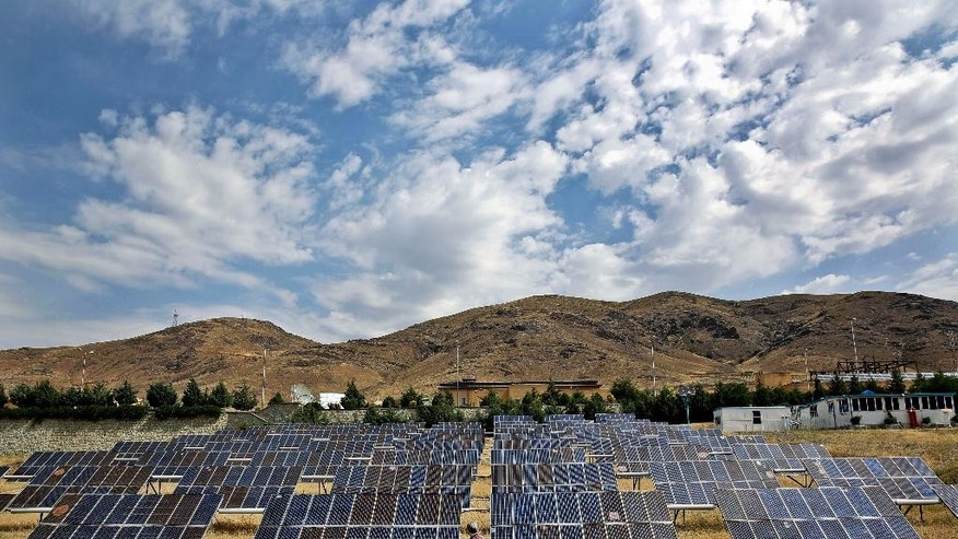 In this June, 22, 2014 photo, a man looks at solar panels at the Taleghan Renewable Energy Site in Taleghan, 160 kilometers (99 miles) northwest of capital Tehran, Iran. President Hassan Rouhani's government has quintupled its spending on solar power projects in the last year, taking advantage of Iran's 300-odd days of sunshine a year that make its vast sun-kissed lands one of the best spots on earth to host solar panels. While being good for the environment, the panels also offer rural Iran steady power amid uncertainty over the country's contested nuclear program as it negotiates with world powers. (AP Photo/Ebrahim Noroozi)