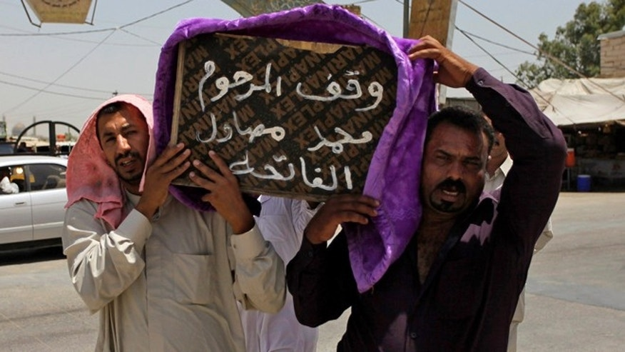 "July 1, 2014: Mourners carry the coffin of a victim of violence before his burial in the Shiite holy city of Najaf, 100 miles south of Baghdad, Iraq. Violence has claimed the lives of 2,417 Iraqis in June, making it the deadliest month so far this year, the United Nations said on Tuesday, underlining the daunting challenge the government faces as it struggles to confront Islamic extremists who have seized large swaths of territory in the north and west. Arabic on the coffin reads, ""they stood for the late Mohammed Mosawel."""